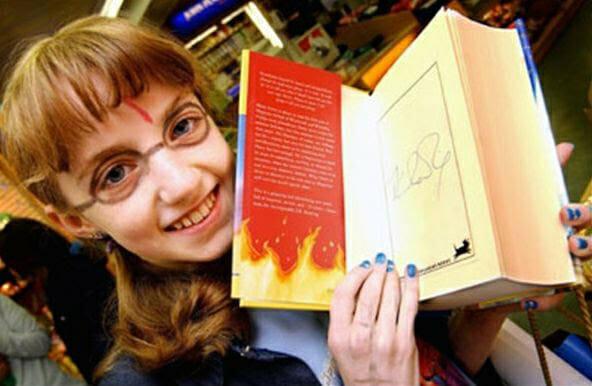Evanna Lynch adolescente segura sua cópia autografada de Harry Potter e a Ordem da Fênix