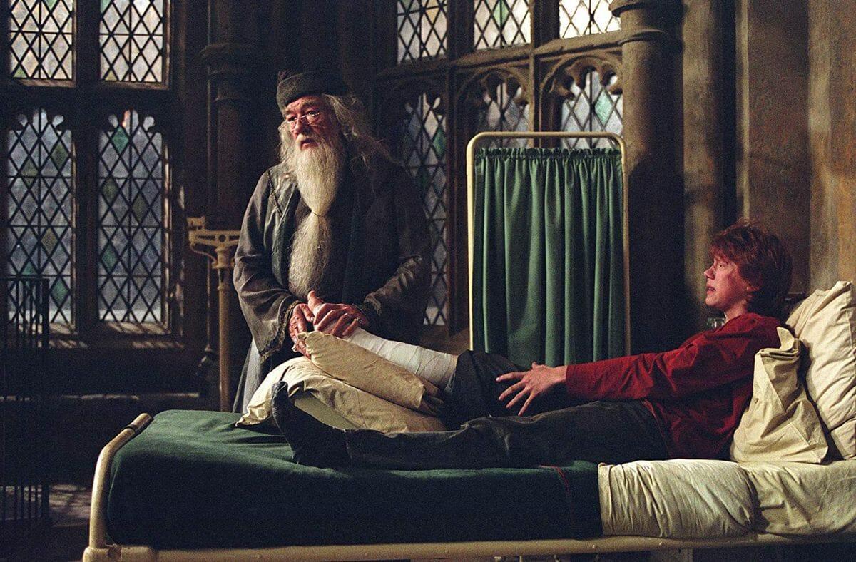 Alvo Dumbledore descansa sua mão na perna machucada de Rony Weasley